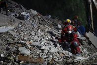 Members of rescue services sit in silence as they search in the debris of a collapsed building for survivors in Izmir, Turkey, Sunday, Nov. 1, 2020. Rescue teams continue ploughing through concrete blocs and debris of collapsed buildings in Turkey's third largest city in search of survivors of a powerful earthquake that struck Turkey's Aegean coast and north of the Greek island of Samos, Friday Oct. 30, killing dozens Hundreds of others were injured.(AP Photo/Emrah Gurel)
