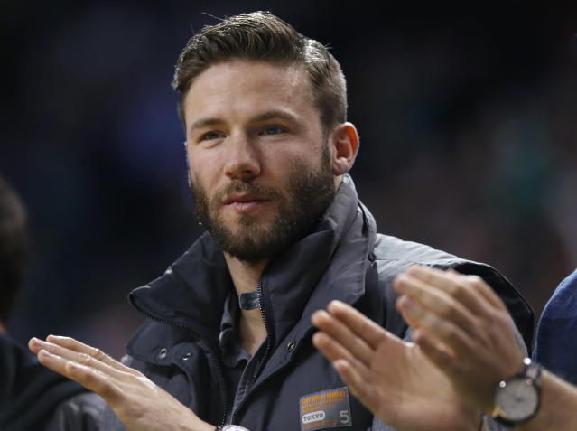 New England Patriots football player Julian Edelman applauds while sitting courtside in the first half of an NBA basketball game between the Boston Celtics and the Houston Rockets in Boston, Monday, Jan. 13, 2014. (AP Photo/Elise Amendola)