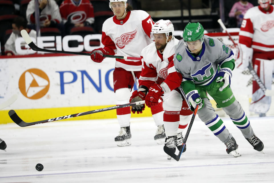 Carolina Hurricanes' Sebastian Aho (20) battles for the puck with Detroit Red Wings' Luke Glendening (41) during the first period of an NHL hockey game in Raleigh, N.C., Saturday, April 10, 2021. (AP Photo/Karl B DeBlaker)