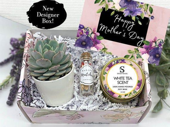 """<p><strong>SweetBasilCo</strong></p><p>etsy.com</p><p><strong>$26.99</strong></p><p><a href=""""https://go.redirectingat.com?id=74968X1596630&url=https%3A%2F%2Fwww.etsy.com%2Flisting%2F974040031%2Fmothers-day-gift-box-candle-gift-box&sref=https%3A%2F%2Fwww.countryliving.com%2Fshopping%2Fgifts%2Fg19663932%2Fmothers-day-gift-baskets%2F"""" rel=""""nofollow noopener"""" target=""""_blank"""" data-ylk=""""slk:Shop Now"""" class=""""link rapid-noclick-resp"""">Shop Now</a></p><p>Treat Mom on her special day with a potted succulent. This pretty gift box comes with a hand-poured soy wax candle, a jar of matches, and a card.</p>"""