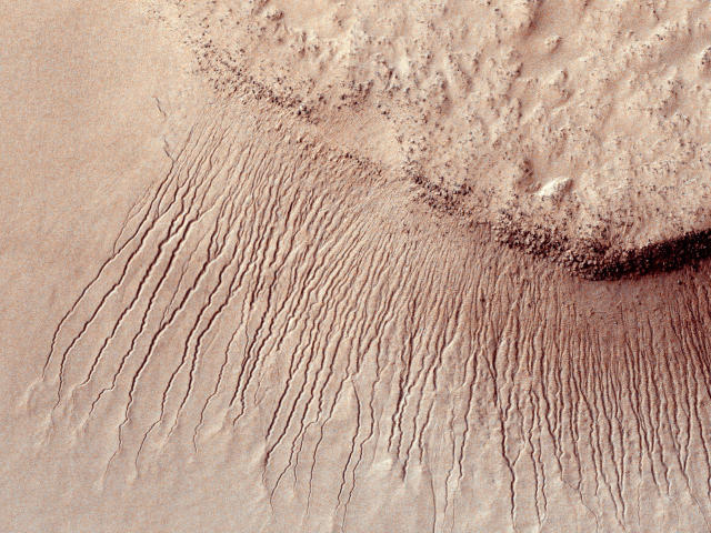 <p>Portions of the Martian surface are pictured, shot by the High Resolution Imaging Science Experiment (HiRISE) camera on NASA's Mars Reconnaissance Orbiter showing many channels from 1 meter to 10 meters wide on a scarp in the Hellas impact basin on Mars. in this photograph taken January 14, 2011 and released by NASA March 9, 2011. (Photo: NASA/JPL-Caltech/Univ. of Arizona/Reuters) </p>