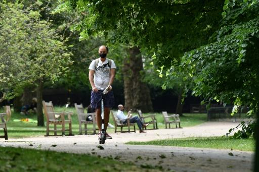 A man wears a facemask as he scooters through  St James's Park in central London on May 26 as lockdown measures are eased