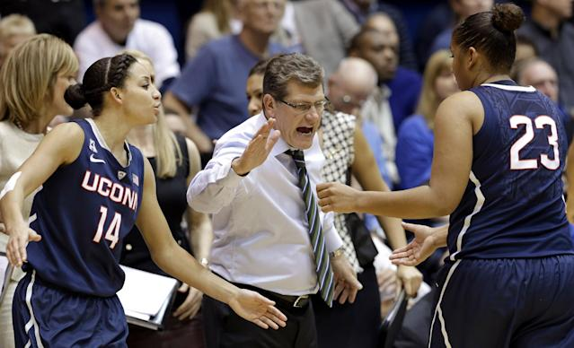Connecticut's Bria Hartley (14) and coach Geno Auriemma congratulate Kaleena Mosqueda-Lewis (23) as Mosqueda-Lewis leaves the court during the second half of an NCAA college basketball game against Duke in Durham, N.C., Tuesday, Dec. 17, 2013. Connecticut won 83-61.(AP Photo/Gerry Broome)
