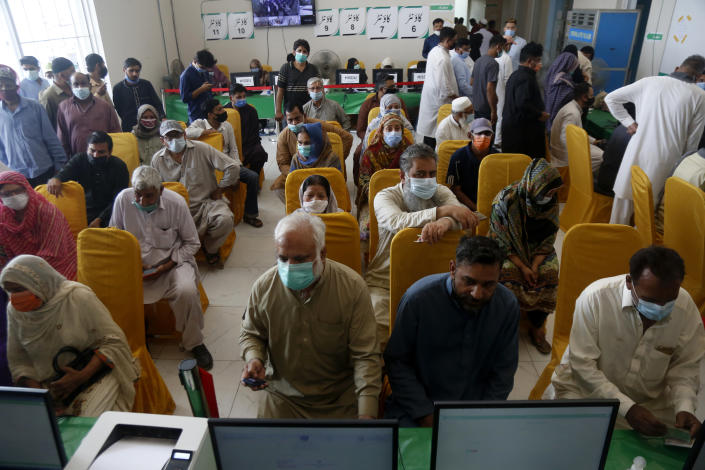 People wait for their turn to receive the second shot of the AstraZeneca COVID-19 vaccine at a vaccination center in Lahore, Pakistan, Sunday, May 16, 2021. (AP Photo/K.M. Chuadary)