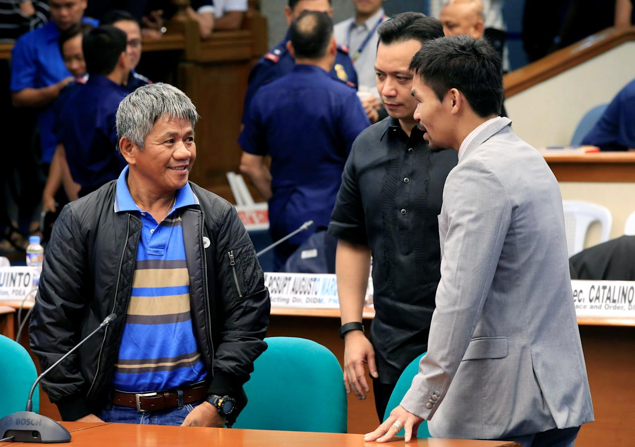 Edgar Matobato (L), a self-confessed former hitman, chats with Senator and boxing champion Manny Pacquiao (R) and Senator Antonio Trillanes before the start of a hearing on drug-related extrajudicial killings at Senate headquarters in Pasay city, Metro Manila, Philippines, September 22, 2016. REUTERS/Romeo Ranoco