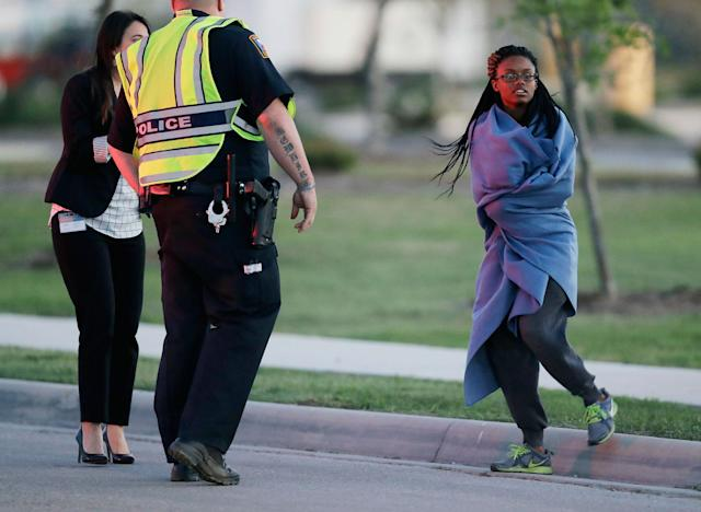 <p>An employee wrapped in a blanket talks to a police officer after she was evacuated at a FedEx distribution center where a package exploded, Tuesday, March 20, 2018, in Schertz, Texas. Authorities believe the package bomb is linked to the recent string of Austin bombings. (Photo: Eric Gay/AP) </p>