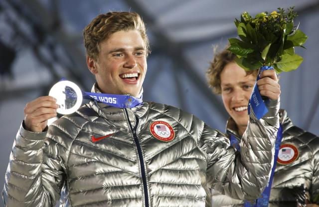 Silver medalist Gus Kenworthy (L) of the U.S. celebrates as his compatriot, gold winner Joss Christensen, watches during the medal ceremony of the men's freestyle skiing slopestyle finals at the 2014 Sochi Winter Olympics, February 13, 2014. REUTERS/Eric Gaillard (RUSSIA - Tags: SPORT OLYMPICS SPORT SKIING)