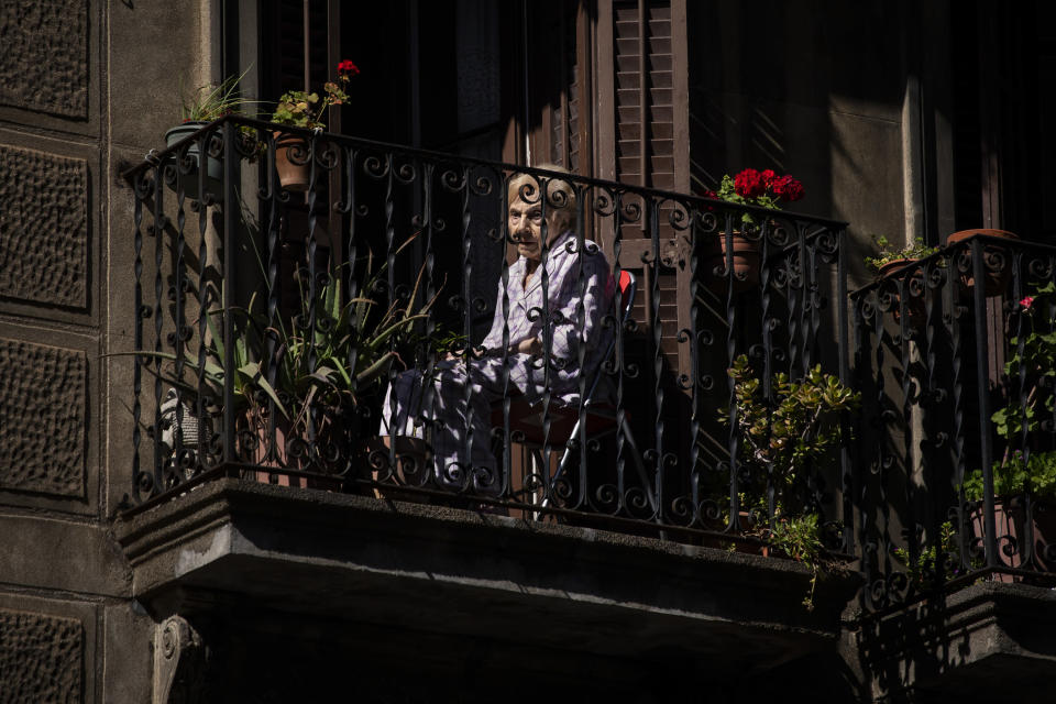 A woman sits on her balcony in downtown Barcelona, Spain, May 7, 2020. The image was part of a series by Associated Press photographer Emilio Morenatti that won the 2021 Pulitzer Prize for feature photography. (AP Photo/Emilio Morenatti)