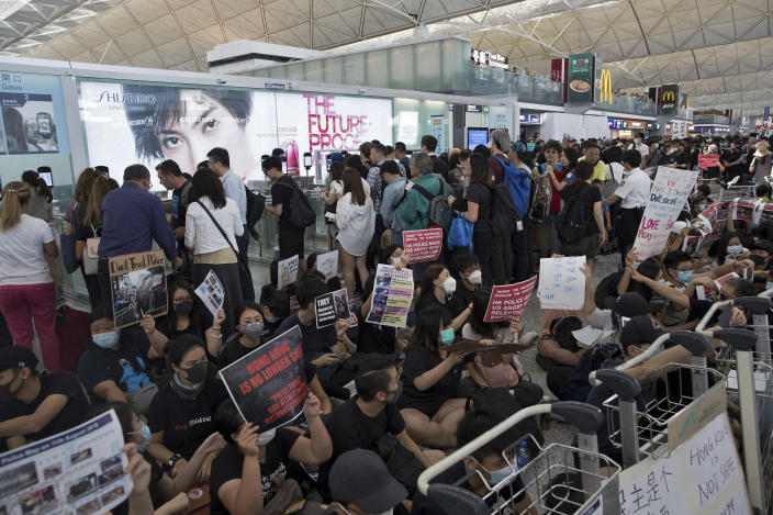 Travelers walk past as protesters hold a sit-in rally near the departure gate of the Hong Kong International Airport in Hong Kong, Tuesday, Aug. 13, 2019. (Photo: Vincent Thian/AP)