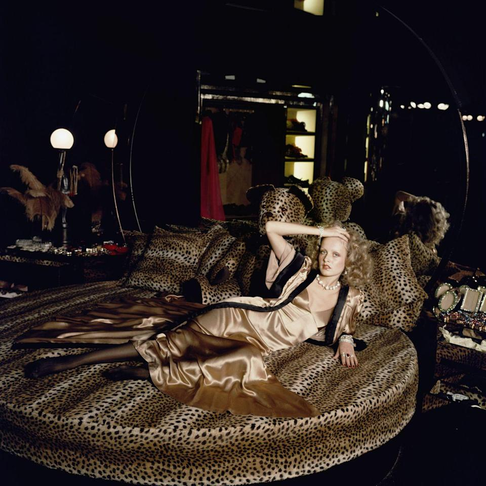 <p>English model Twiggy poses on a circular bed with leopard print bedding in a satin evening gown in 1971. </p>