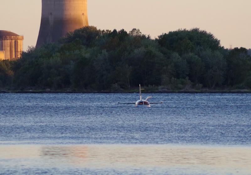 A small plane sits in in a shallow section of the Susquehanna River a few miles from the Three Mile Island nuclear power station after landing on an approach to a Pennsylvania airport,  Friday, Oct. 4, 2019 near Middletown, Pa. Susquehanna Regional Airport Authority executive director Tim Edwards said the pilot and the single-engine plane's lone passenger were taken to a hospital for treatment. The Federal Aviation Administration says the two on board exited the Piper PA-46 onto a wing.(Garrett Doane/The Sun via AP)