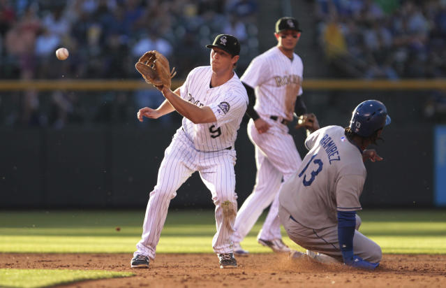 Los Angeles Dodgers shortstop Hanley Ramirez (13) safely steals second base against Colorado Rockies second baseman DJ LeMahieu (9) in the second inning of a baseball game in Denver on Friday, June 6, 2014. (AP Photo/Joe Mahoney)