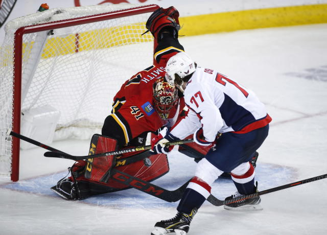 Washington Capitals' T.J. Oshie, right, has his shot blocked by Calgary Flames goalie Mike Smith during second period NHL hockey action in Calgary, Alberta, Saturday, Oct. 27, 2018. (Jeff McIntosh/The Canadian Press via AP)