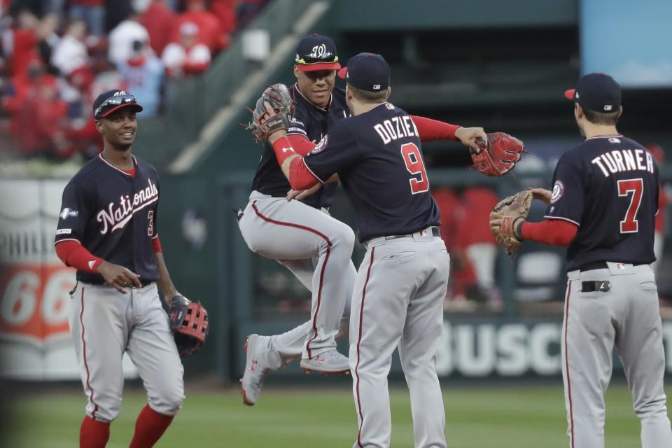 Washington Nationals' Juan Soto and Brian Dozier celebrate after Game 2 of the baseball National League Championship Series against the St. Louis Cardinals Saturday, Oct. 12, 2019, in St. Louis. The Nationals won 3-1 to take a 2-0 lead in the series. (AP Photo/Mark Humphrey)
