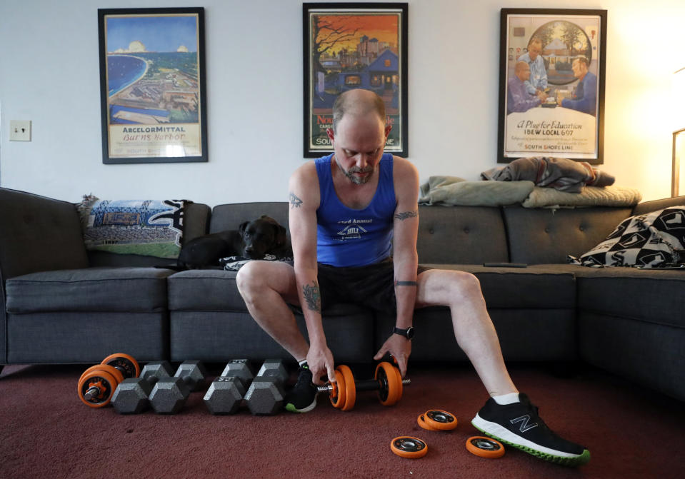 Christian Hainds prepares for a workout session at his home in Hammond, Ind., Monday, June 7, 2021. Health officials have warned since early on in the pandemic that obesity and related conditions such as diabetes were risk factors for severe COVID-19. It wasn't until he was diagnosed as diabetic around the start of the pandemic that he felt the urgency to make changes. Hainds lost about 50 pounds during the pandemic, and at 180 pounds and 5 feet, 11 inches tall is no longer considered obese. (AP Photo/Shafkat Anowar)