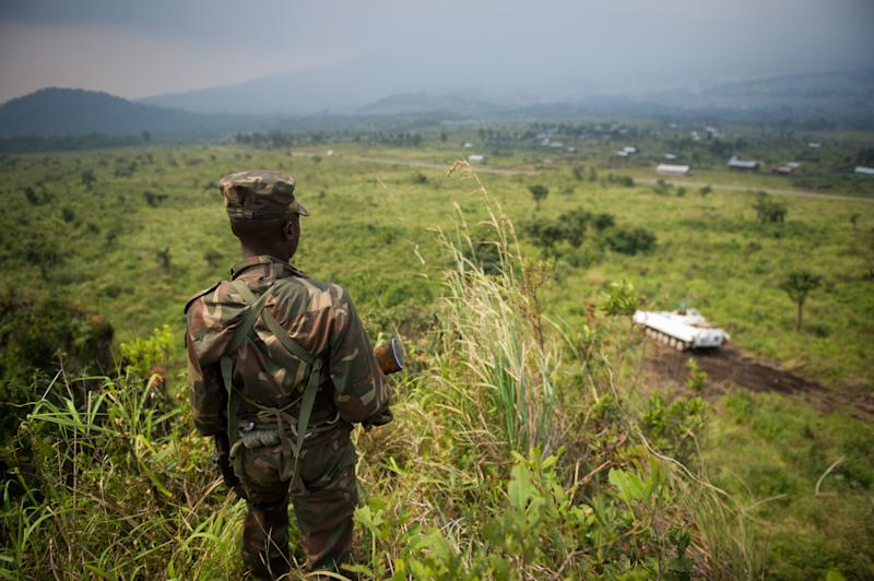 A soldier from the Armed Forces of the Democratic Republic of the Congo stands guard on a hill overlooking a United Nations tank position near the village of Kibumba I, in the restive North Kivu province on July 11, 2012 (AFP Photo/Phil Moore)