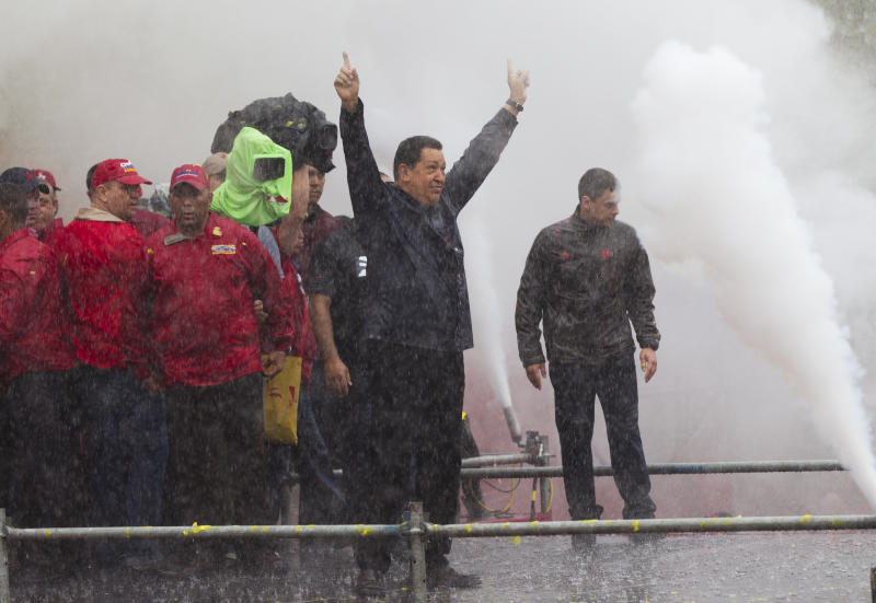Under pouring rain, Venezuela's President Hugo Chavez, second from right, gestures to supporters during his closing campaign rally in Caracas, Venezuela, Thursday, Oct. 4, 2012. Chavez is running for re-election against opposition candidate Henrique Capriles in presidential elections on Oct . 7. (AP Photo/Ariana Cubillos)