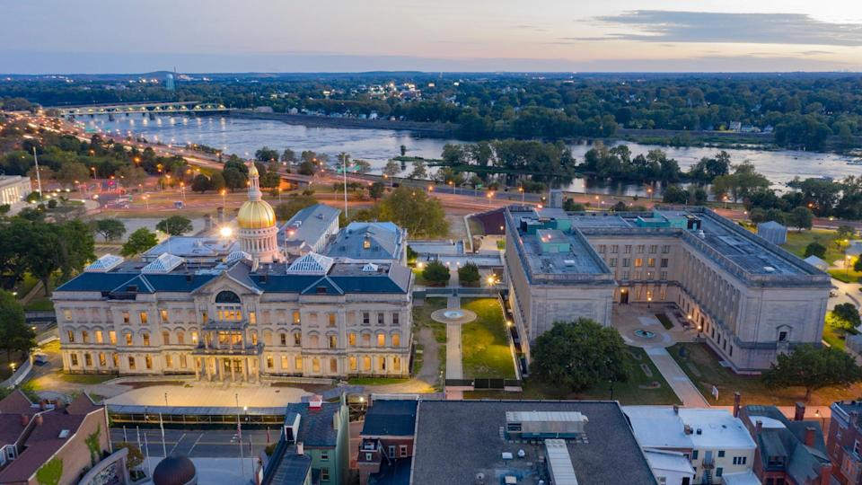 The capital statehouse of New Jersey lights up as the sun sets the Delaware River in the background city of Trenton.