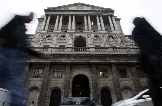 Pedestrians pass by The Bank of England building in London. (Kirsty Wigglesworth/AP)