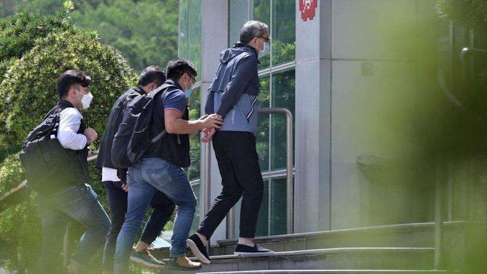 Cheung Kim Hung (C), CEO and Executive Director of Next Digital Ltd, is escorted by police into the Apple Daily newspaper offices in Hong Kong