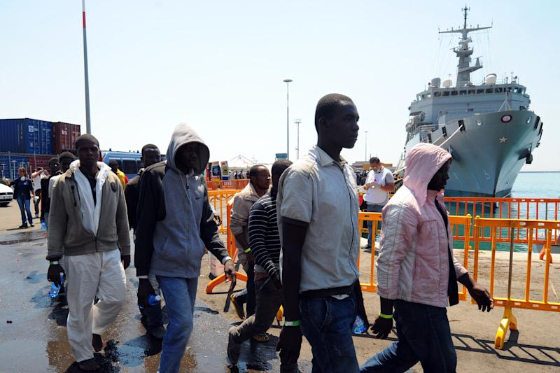 """Migrants disembark from Italian military ship """"Etna"""" on July 19, 2014 in the port of Salerno, southern Italy, following a rescue operation (AFP Photo/Mario Laporta)"""