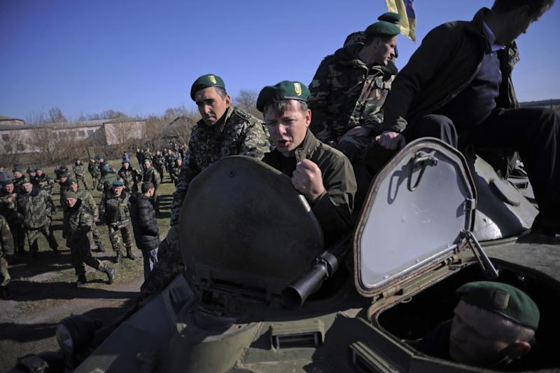 In this photo taken on Saturday, April 5, 2014, Oleh Lyashko, center, leader of Ukrainian Radical Party and presidential candidate who supported the protests that ousted Russian-leaning president Viktor Yanukovych, gestures atop of a military vehicle during his visit to Ukrainian troops at their camp near Ukraine-Russian border outside Chernihiv, 140km (87 miles) northeast of Kiev, Ukraine. Ukraine's security service said Saturday it has detained a 15-strong armed gang planning to seize power in an eastern province on the border with Russia. (AP Photo/Osman Karimov)