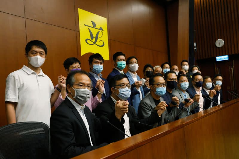 Pan-democratic legislators including Alvin Yeung, Dennis Kwok and Wu Chi-wai join their hands during a news conference as they threat with mass resignations amid reports on Beijing plans to disqualify four opposition lawmakers, in Hong Kong