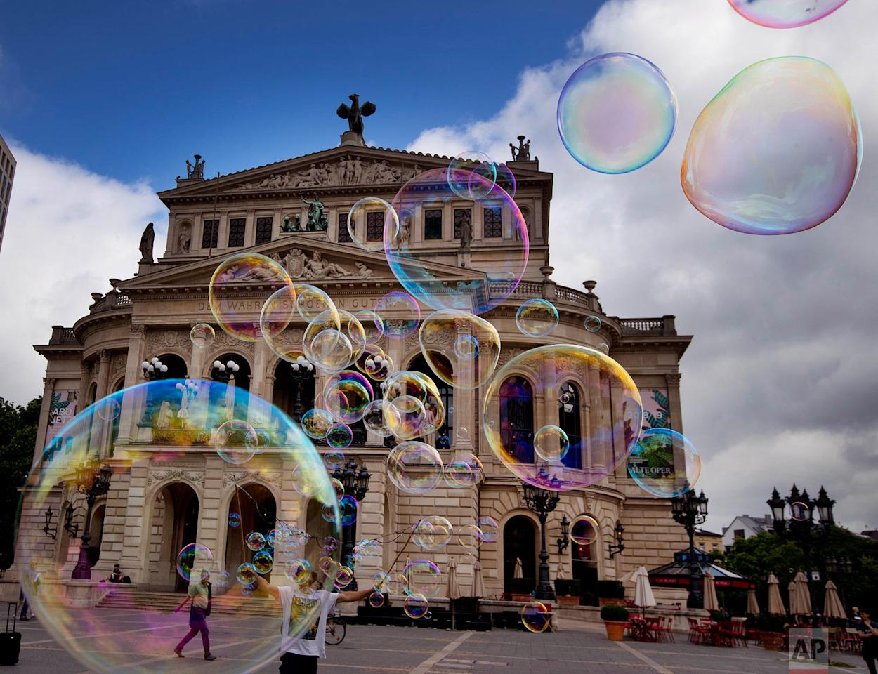 <p>A bubble artist performs with soap bubbles in front of the Old Opera in Frankfurt, Germany. (AP Photo/Michael Probst) </p>
