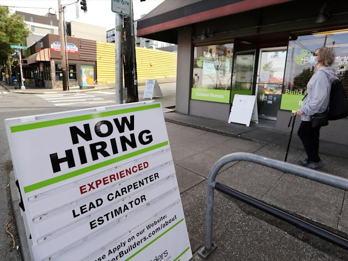 In this photo taken Thursday, June 4, 2020, a pedestrian wearing a mask walks past reader board advertising a job opening for a remodeling company, in Seattle. The U.S. unemployment rate fell to 13.3% in May, and 2.5 million jobs were added — a surprisingly positive reading in the midst of a recession that has paralyzed the economy and depressed the job market in the wake of the viral pandemic. (AP Photo/Elaine Thompson)