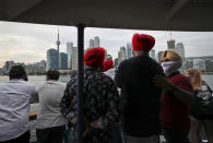People look at the city skyline on a ferry coming back from Centre Island to Toronto, Canada, Saturday, July 17, 2021. With nearly 70% of its adult population receiving at least one dose of a COVID-19 vaccine, Canada has the world's highest vaccination rate and is now moving on to immunize children, who are at far lower risk of coronavirus complications and death. (AP Photo/Kamran Jebreili)