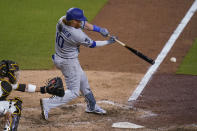 Los Angeles Dodgers' Justin Turner hits an RBI single during the ninth inning of the team's baseball game against the San Diego Padres, Friday, April 16, 2021, in San Diego. (AP Photo/Gregory Bull)