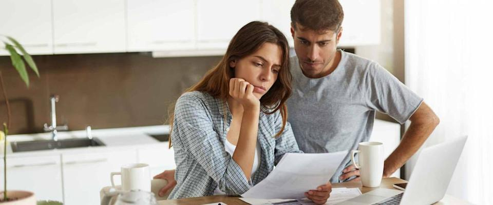 Picture of young wife and husband in kitchen looking for a mortgage refinance