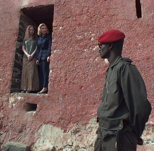 "FILE - In this March 17, 1997, file photo, as a Senegalese guard looks on, first lady Hillary Rodham Clinton and daughter Chelsea look out from ""the door of no return"" on Goree Island in Dakar, Senegal. This is the door through which more than 60,000 slaves walked before being shipped to the west and used as slaves. Mrs. Clinton is on the first day of her two-week goodwill tour through Africa. When Melania Trump flies to Africa on her first extended international journey without the president, she'll be following in the footsteps of her recent predecessors. (AP Photo/Doug Mills)"