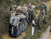German soldiers work on a flooded car on a road in Erftstadt, Germany, Saturday, July 17, 2021. Due to strong rainfall, the small Erft river went over its banks causing massive damage. (AP Photo/Michael Probst)