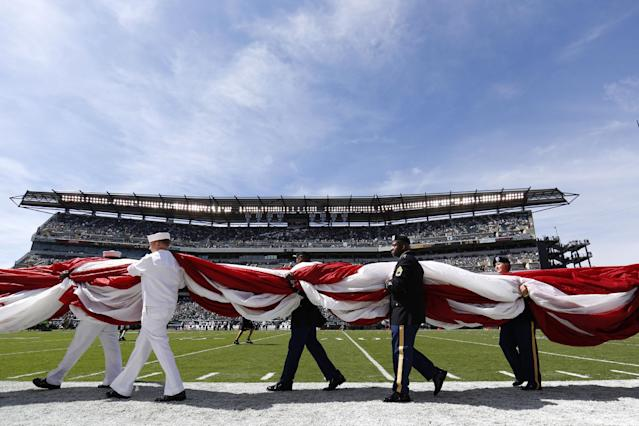 Military personnel carry an American flag on to the field before an NFL football game between the Philadelphia Eagles and the San Diego Chargers, Sunday, Sept. 15, 2013, in Philadelphia. (AP Photo/Matt Rourke)