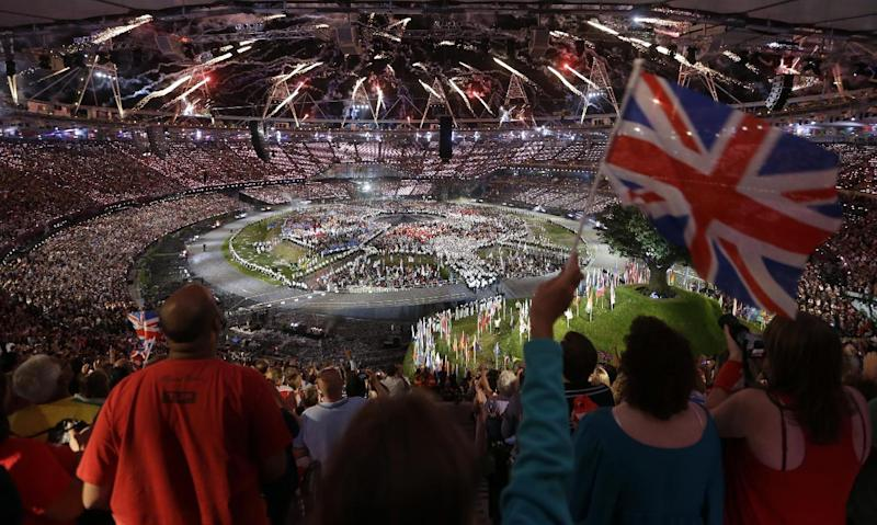 A spectator waves a flag of Great Britain as pyrotechnics light up the sky over the Olympic Stadium during the Opening Ceremony at the 2012 Summer Olympics, Friday, July 27, 2012, in London. (AP Photo/Markus Schreiber)