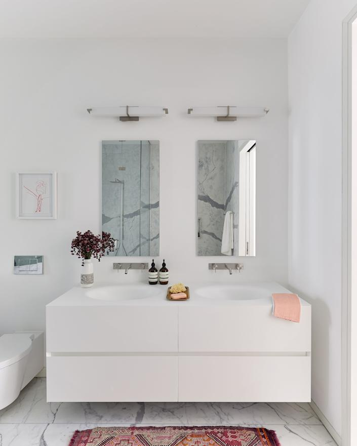 """<div class=""""caption""""> Bergin infused the master bath with personality thanks to fixtures by <a href=""""https://ceadesign.it/it/home.html"""" rel=""""nofollow noopener"""" target=""""_blank"""" data-ylk=""""slk:Cea Design"""" class=""""link rapid-noclick-resp"""">Cea Design</a>, a hand towel by <a href=""""https://rikumo.com/"""" rel=""""nofollow noopener"""" target=""""_blank"""" data-ylk=""""slk:Rikumo"""" class=""""link rapid-noclick-resp"""">Rikumo</a>, a vase by <a href=""""https://www.heathceramics.com/"""" rel=""""nofollow noopener"""" target=""""_blank"""" data-ylk=""""slk:Heath Ceramics"""" class=""""link rapid-noclick-resp"""">Heath Ceramics</a>, and a vintage Turkish rug purchased on <a href=""""https://www.etsy.com/"""" rel=""""nofollow noopener"""" target=""""_blank"""" data-ylk=""""slk:Etsy"""" class=""""link rapid-noclick-resp"""">Etsy</a>. </div>"""