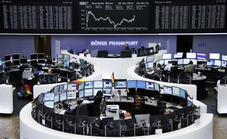 Traders are pictured at their desks in front of the DAX board at the Frankfurt stock exchange June 30, 2014. REUTERS/Remote/Thomas Peter