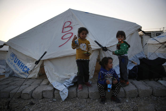 Syrian children who are newly displaced by the Turkish military operation in northeastern Syria, stand outside their tent at the Bardarash camp, north of Mosul, Iraq, Wednesday, Oct. 16, 2019. The camp used to host Iraqis displaced from Mosul during the fight against the Islamic State group and was closed two years ago. The U.N. says more around 160,000 Syrians have been displaced since the Turkish operation started last week, most of them internally in Syria. (AP Photo/Hussein Malla)