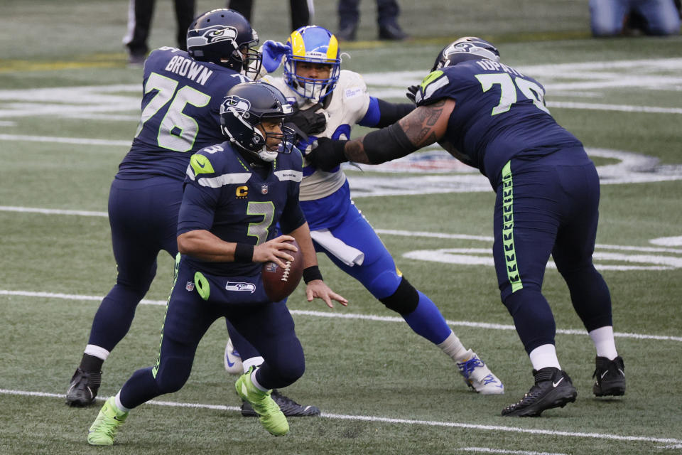 Russell Wilson of the Seattle Seahawks scrambles against defensive end Aaron Donald of the Los Angeles Rams during the NFC wild-card game on Jan. 09, 2021. (Steph Chambers/Getty Images)