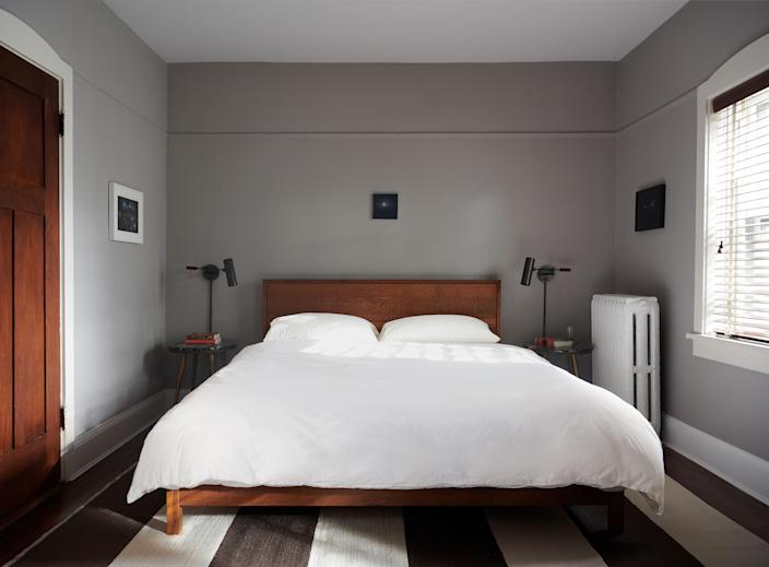 """The couple's bed is by Matt Seidel of <a href=""""https://www.mabbottseidel.com/"""">Mabbott Seidel</a> Architecture; wall lamps by <a href=""""https://apparatusstudio.com/"""">Apparatus.</a>"""