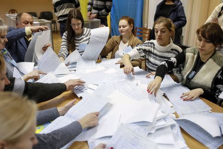 Members of a local electoral commission count ballots at a polling station after voting day in Kiev, October 26, 2014. REUTERS/Gleb Garanich