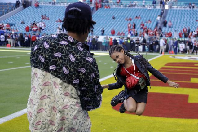 Entertainer Jay-Z watches his daughter Blue Ivy Carter leap on the field before the NFL Super Bowl 54 football game between the San Francisco 49ers and the Kansas City Chiefs, Sunday, Feb. 2, 2020, in Miami. (AP Photo/David J. Phillip)