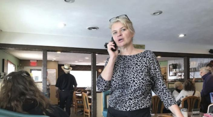Marlena Pavlos-Hackney talks on a cell phone at her Holland restaurant, Marlena's Bistro & Pizzeria, on Thursday, March 18, 2021, in Holland, Mich. Michigan State Police arrested Pavlos-Hackney on Friday, March 19, 2021. State investigators say she ignored caps on restaurant capacity and wasn't enforcing mask rules. Her food license was suspended Jan. 20, but the eatery remained open. (John Agar/The Grand Rapids Press via AP)