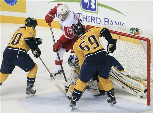 Detroit Red Wings center Pavel Datsyuk (13), of Russia, scores against Nashville Predators goalie Pekka Rinne, of Finland, as Predators defenders Ryan Suter (20) and Roman Josi (47), of Switzerland, close in during the second period of an NHL hockey game on Monday, Dec. 26, 2011, in Nashville, Tenn. (AP Photo/Mark Humphrey)