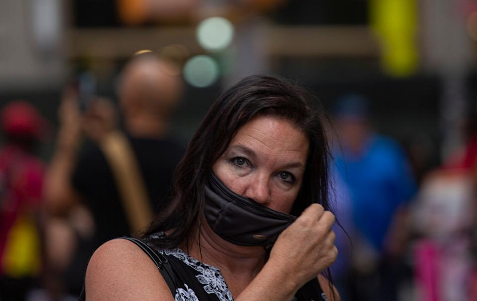 A woman wears a face mask in Midtown Manhattan in New York on July 29 2021. - Every US federal worker must either declare they are fully vaccinated against Covid-19 or wear masks and be regularly tested, President Joe Biden was to announce July 29, 2021, the White House said, as his administration beefs up actions against the surging delta variant. The governors of New York and New Jersey on July 28, 2021 publicly backed the idea of indoor masking for vaccinated people in high Covid-19 risk areas. (Photo by Kena Betancur / AFP) (Photo by KENA BETANCUR/AFP via Getty Images)