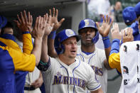 Seattle Mariners Kyle Seager, left, and Kyle Lewis are congratulated in the dugout after scoring against the Texas Rangers in the third inning of a baseball game Sunday, May 30, 2021, in Seattle. (AP Photo/Elaine Thompson)