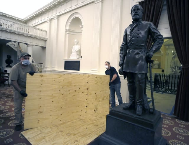 Workmen place plywood beside the statue of Robert E. Lee in the Old House Chambe (Bob Brown/PA)