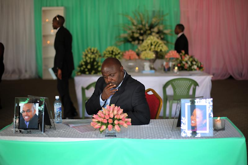 A man sits at a table with a photo of Mbugua Mwangi, at left and his fiancee Rosemary Wahito, in photo at right, during their funeral service in Nairobi, Kenya, Friday Sept. 27, 2013. Mwangi, who is Kenyan President Uhuru Kenyatta's nephew, and Wahito died in the Westgate Mall attack that killed more than 60 people. (AP Photo/Jerome Delay)