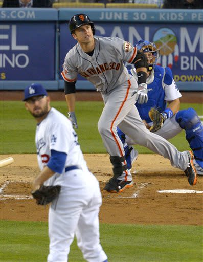 San Francisco Giants' Buster Posey, center, watches his solo home run off Los Angeles Dodgers starting pitcher Stephen Fife, left, as catcher Tim Federowicz follows the baseball during the fourth inning of a baseball game, Tuesday, June 25, 2013, in Los Angeles. (AP Photo/Mark J. Terrill)